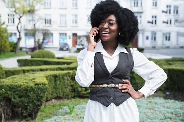 Gelukkig portret van een afrikaanse jonge zakenvrouw met zijn hand op de heupen praten op mobiele telefoon Gratis Foto