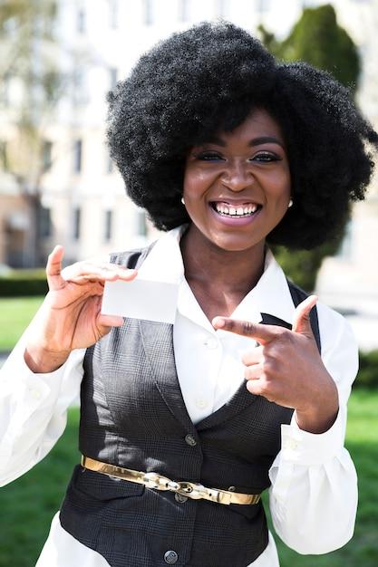 Gelukkig portret van een afrikaanse jonge zakenvrouw wijzende vinger naar visitekaartje Gratis Foto