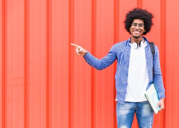 Gelukkig portret van een mannelijke student die zijn vinger richt die zich tegen een heldere muur bevindt Gratis Foto