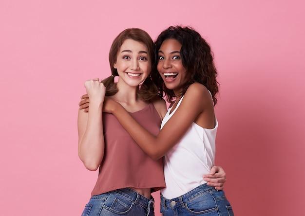 Gelukkig portret van jonge vrouw twee en omhelzing samen over roze. Premium Foto