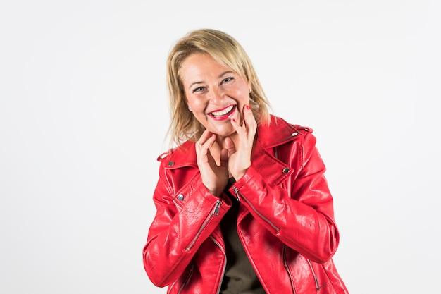 Gelukkig portret van volwassen vrouw in rode jas geïsoleerd op een witte achtergrond Gratis Foto