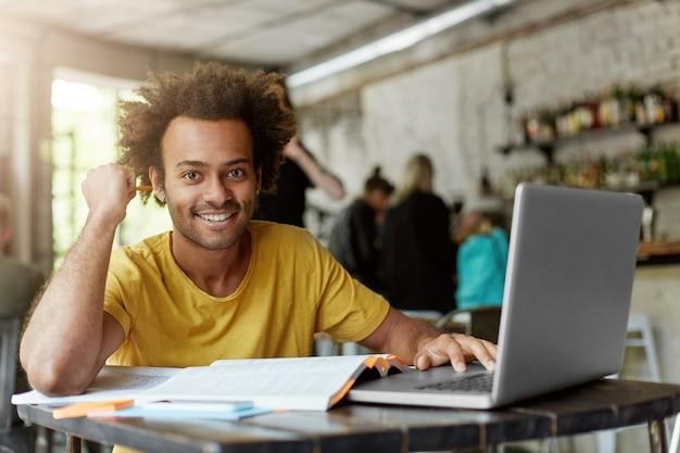 Gelukkig positieve afro-amerikaanse student met vrolijke schattige glimlach met behulp van draadloze internetverbinding op laptopcomputer bij coffeeshop tijdens het zoeken naar informatie online voor onderzoeksproject Gratis Foto