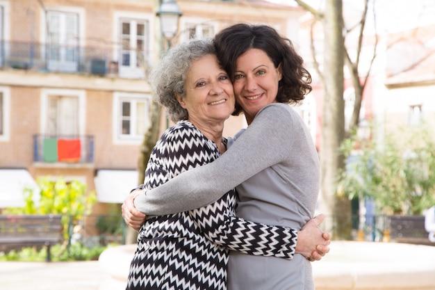 Gelukkig positieve jonge vrouw poseren met haar moeder Gratis Foto