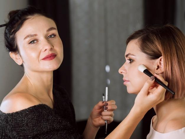 Gelukkig professionele make-up artist aan het werk Gratis Foto