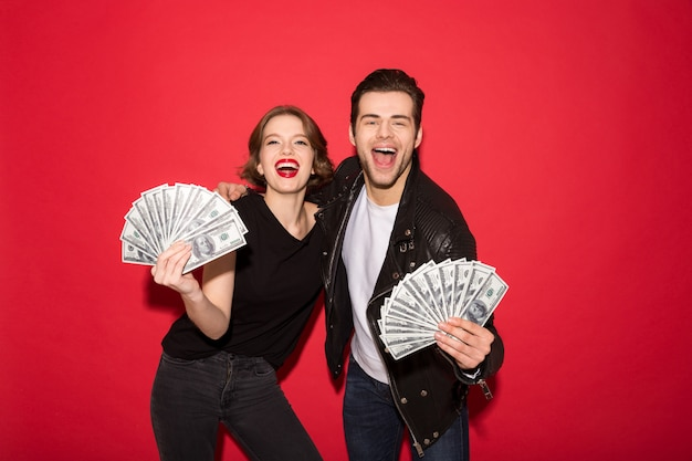 Gelukkig punk paar dat geld en het kijken toont Gratis Foto