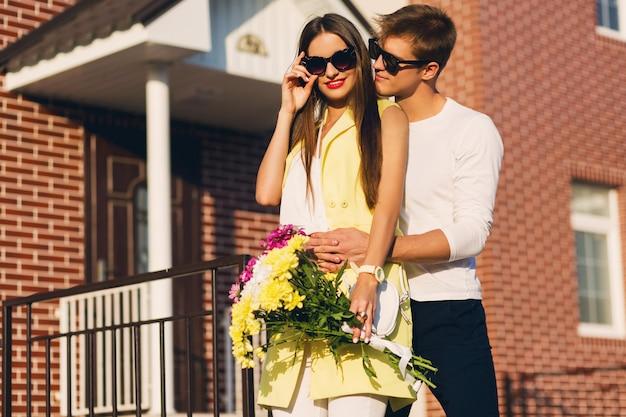 Gelukkig romantisch paar die in openlucht in europese stad bij de avond omhelzen. jonge mooie vrouw met bloemen. verliefde paar dating. Gratis Foto