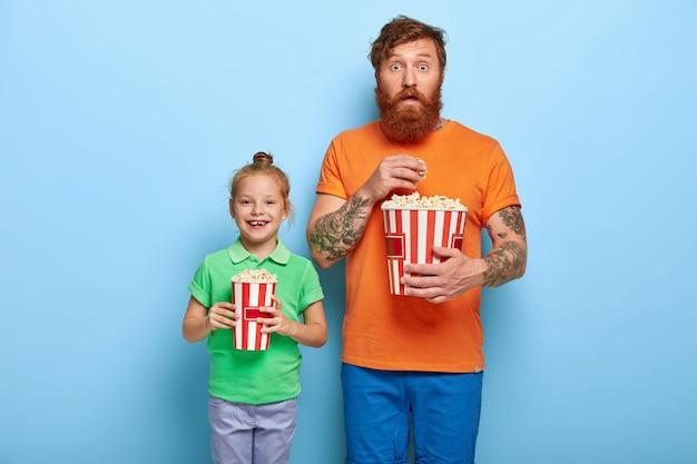 Gelukkig roodharig kind en haar vader houden emmers smakelijke popcorn vast Gratis Foto