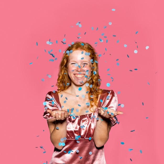 Gelukkig roodharige meisje confetti gooien Gratis Foto