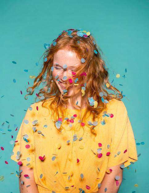 Gelukkig roodharige vrouw feesten met confetti in haar haar Gratis Foto