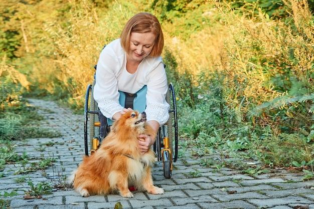 Gelukkig roodharige vrouw in een rolstoel voor een wandeling met haar hond, genietend van zonnig weer in de herfst. Premium Foto