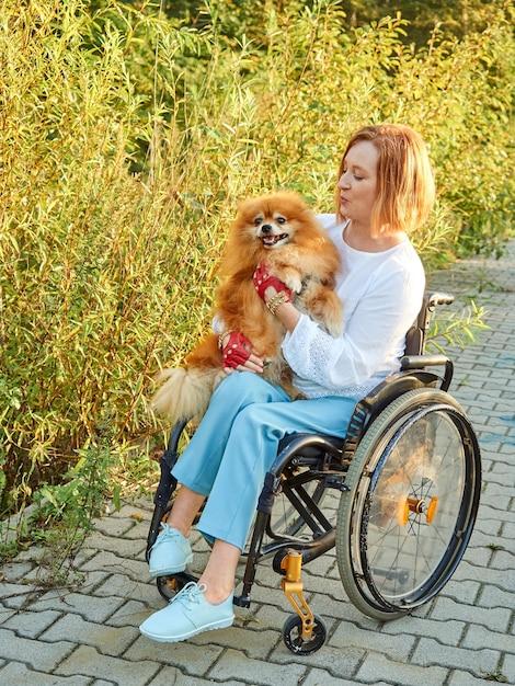 Gelukkig roodharige vrouw in een rolstoel voor een wandeling met haar hond. internationale dag van mensen met een handicap Premium Foto
