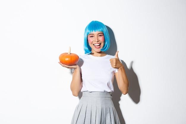 Gelukkig schattig aziatisch meisje dat halloween viert, feestkostuum en pruik draagt, kleine pompoen houdt, in goedkeuring duimen toont. Gratis Foto