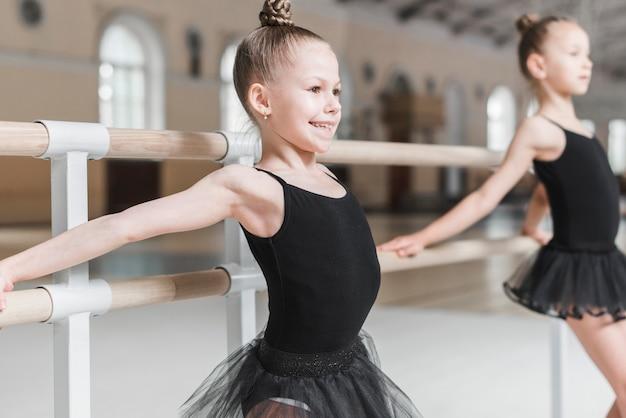 Gelukkig schattig ballerina meisje oefenen bij barre Gratis Foto