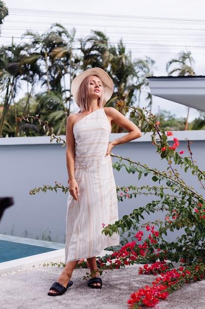 Gelukkig schattig romantisch blanke vrouw in zomer elegante witte open rug jurk, strooien hoed Gratis Foto