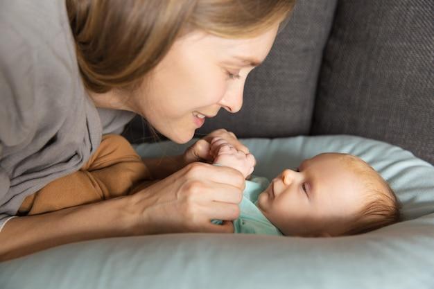 Gelukkig schattige nieuwe moeder praat met haar baby Gratis Foto