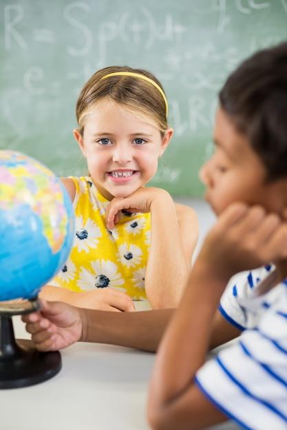 Gelukkig schoolkinderen met globe in de klas Premium Foto
