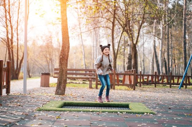 Gelukkig schoolmeisje dat op een kleine trampoline in het park springt Gratis Foto