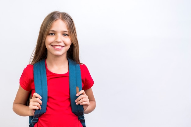 Gelukkig schoolmeisje die met rugzak bij camera glimlachen Gratis Foto