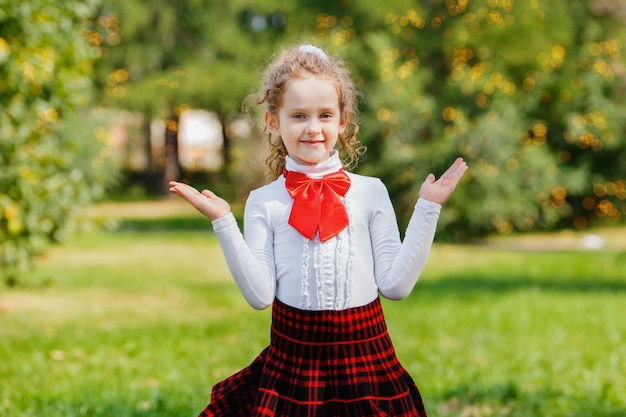 Gelukkig schoolmeisje in school uniforme sprong in het park Premium Foto