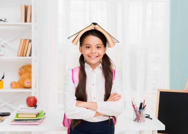 Gelukkig schoolmeisje met boek op hoofd Gratis Foto