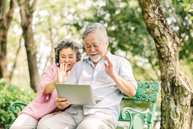 Gelukkig senior aziatisch paar zwaaiende hand om de liefde te begroeten tijdens het gebruik van laptop buiten in het park Premium Foto