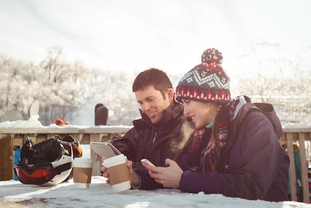 Gelukkig skiër paar zittend aan de tafel tijdens het gebruik van mobiele telefoon en digitale tablet Gratis Foto
