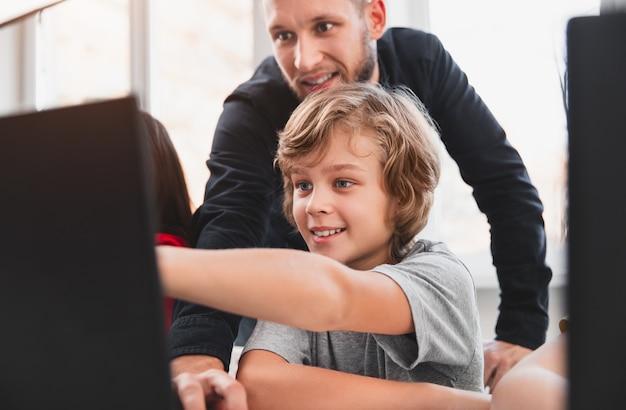 Gelukkig slimme jongen wijzend op laptop scherm terwijl project bespreken met leraar tijdens les programmeren in de klas Premium Foto
