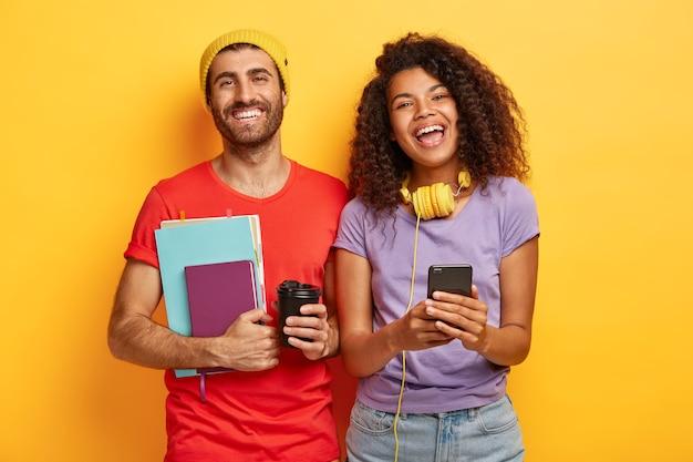 Gelukkig stijlvol paar poseren tegen de gele muur met gadgets Gratis Foto