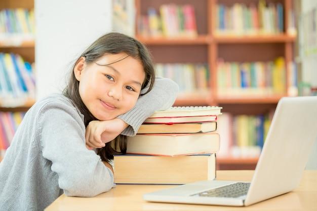 Gelukkig student meisje of jong meisje met boek in bibliotheek. Gratis Foto