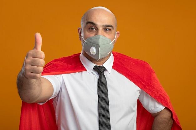 Gelukkig superheld zakenman in beschermend gezichtsmasker en rode cape duimen opdagen Gratis Foto