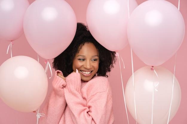 Gelukkig tevreden vrouw met krullend haar met veel ballonnen Premium Foto