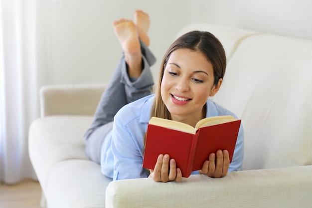 Gelukkig tienermeisje dat op bank in de woonkamer ligt terwijl het lezen van haar favoriete auteur van boeken Premium Foto