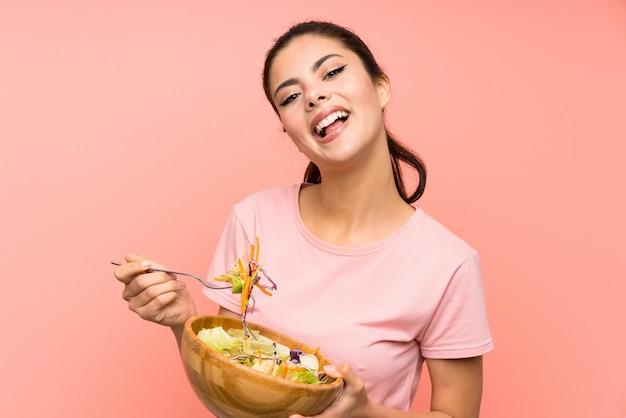 Gelukkig tienermeisje over geïsoleerde roze muur met salade Premium Foto