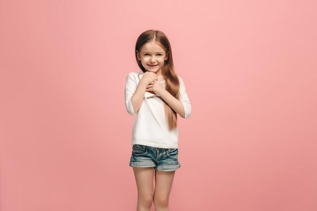Gelukkig tienermeisje staan, glimlachend met mobiele telefoon over trendy roze muur. mooi vrouwelijk portret van halve lengte. menselijke emoties, gezichtsuitdrukking concept. Gratis Foto