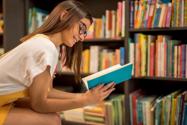 Gelukkig tienerschoolmeisje dat van boek geniet Gratis Foto