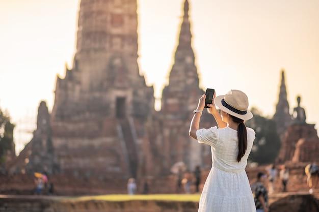 Gelukkig toeristische vrouw in witte jurk foto nemen door mobiele smartphone, tijdens een bezoek aan de wat chaiwatthanaram tempel in ayutthaya historical park, zomer, solo, azië en thailand reizen concept Premium Foto