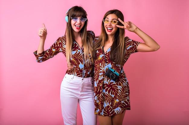 Gelukkig twee beste vrienden zus meisjes plezier tonen ok wetenschap, kleur bijpassende tropische print kleding, kleurrijke moderne zonnebril, grote koptelefoon en vintage camera, studentenfeest. Gratis Foto