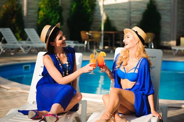 Gelukkig twee meisjes zonnebaden in de buurt van het zwembad op strandstoelen Premium Foto