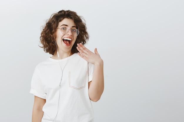 Gelukkig uitgaande jonge vrouw lachen en glimlachen witte tanden, muziek luisteren in de koptelefoon, oortelefoons dragen om te communiceren Gratis Foto