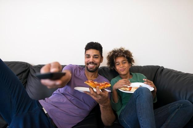 Gelukkig vader en dochter kijken naar favoriete tv-show en genieten van pizzaplak Gratis Foto