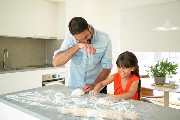 Gelukkig vader en dochter plezier tijdens het kneden van deeg op de keukentafel. vader leert zijn meisje brood of taarten bakken. familie koken concept Gratis Foto