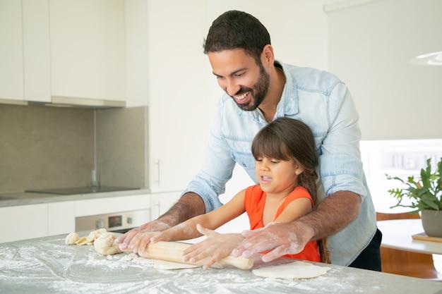 Gelukkig vader en dochter rollend deeg op keukentafel met rommelig bloem. Gratis Foto