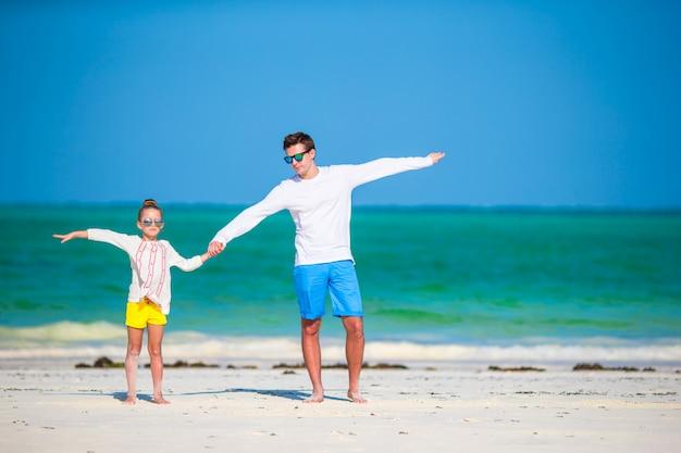Gelukkig vader en kind samen op wit tropisch strand Premium Foto