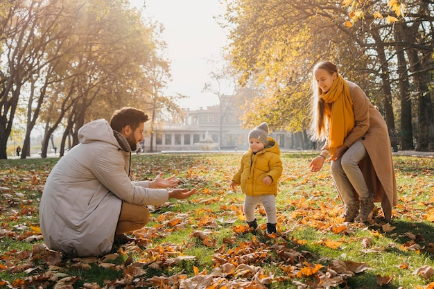 Gelukkig vader en moeder spelen met baby buiten Gratis Foto