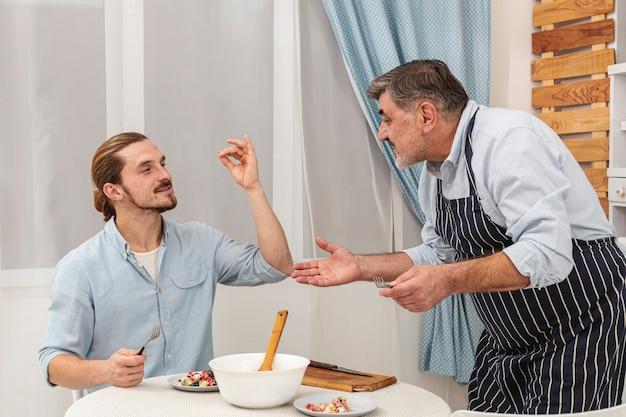 Gelukkig vader en zoon dienend diner Gratis Foto