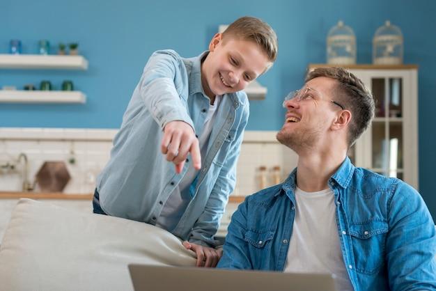Gelukkig vader en zoon met behulp van de laptop Gratis Foto