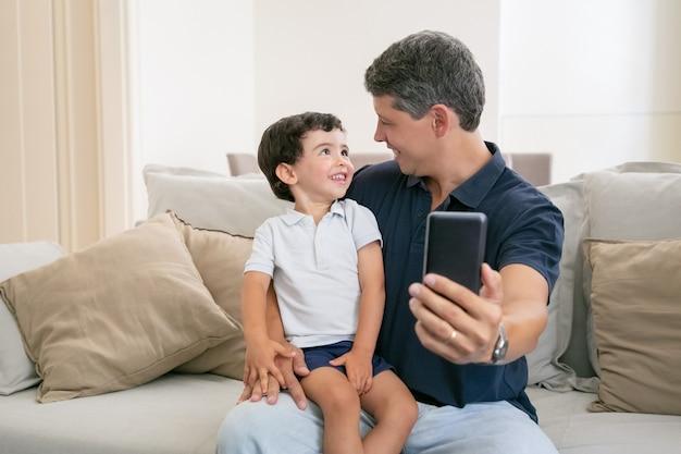 Gelukkig vader en zoontje genieten van tijd samen, zittend op de bank thuis, chatten, lachen en selfie te nemen. Gratis Foto