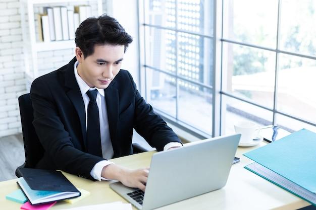 Gelukkig van aziatische jonge zakenman zie een succesvol businessplan op de laptopcomputer en pen op houten tafel achtergrond in kantoor, het bedrijfsleven sprak zijn vertrouwen uit Premium Foto