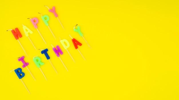 Gelukkig verjaardagsbericht met kleurrijke kaarsen en exemplaarruimte Gratis Foto