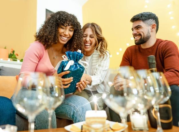 Gelukkig verjaardagsmoment met multiraciale echte mensen thuis lachen vieren met champagne Premium Foto